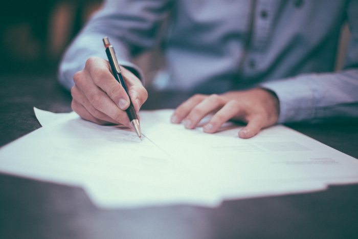 Man signing papers with black and gold pen