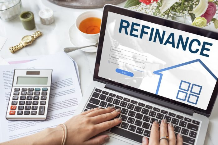 Woman on a laptop with the screen reading Refinance
